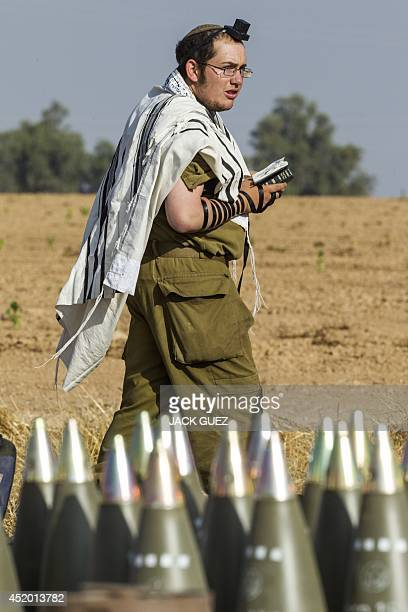 An Israeli soldier wearing a Talit and Tefilin performs morning prayers near a 155mm shells along the southern Israeli border with the Gaza Strip...