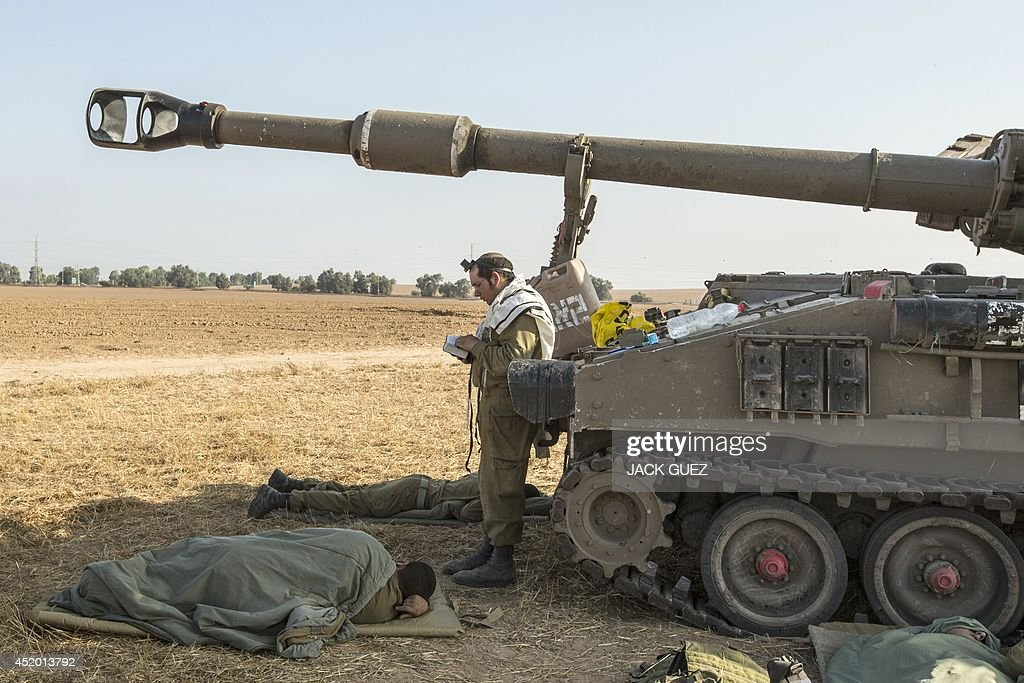 An Israeli soldier wearing a 'Talit' (prayer shawl) and 'Tefilin' (phylacteries) performs morning prayers near a 155mm mobil artillery cannon stationed along the southern Israeli border with the Gaza Strip following Israeli air strikes on the Gaza Strip on July 11, 2014. Since the start of operation 'Protective Edge', the Israeli military's biggest offensive on Gaza since November 2012, its forces have hit over 1090 'terror sites' killing some 95 Palestinians including women and children. In the same period, Gaza militants fired 407 mortars and rockets that struck Israel, while another 118 rockets were intercepted, an army spokeswoman said.