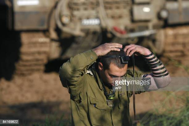 An Israeli soldier wears phylacteries during a morning prayer in a deployment area near the Israeli border with the Gaza Strip on January 2 2009...