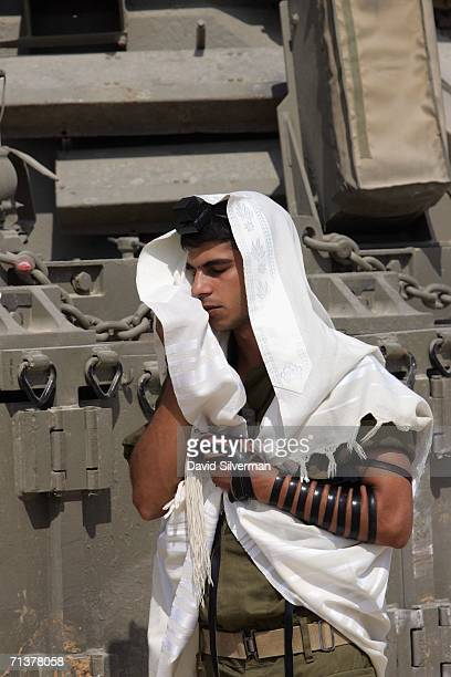An Israeli soldier wraps himself in his prayer shawl as he recites his Jewish morning prayers shortly after his armored personnel carrier returned...