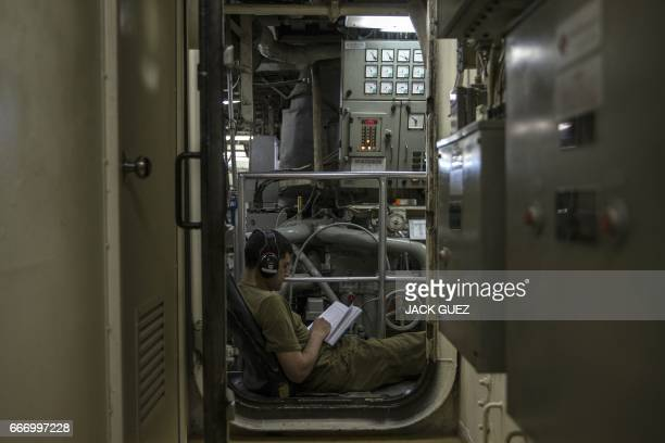 """An Israeli soldiers onboard the Israeli vessel Saar 5 Class Corvette """"INS Hanit"""" reads after a training session during the """"Novel Dina 17"""" exercise..."""