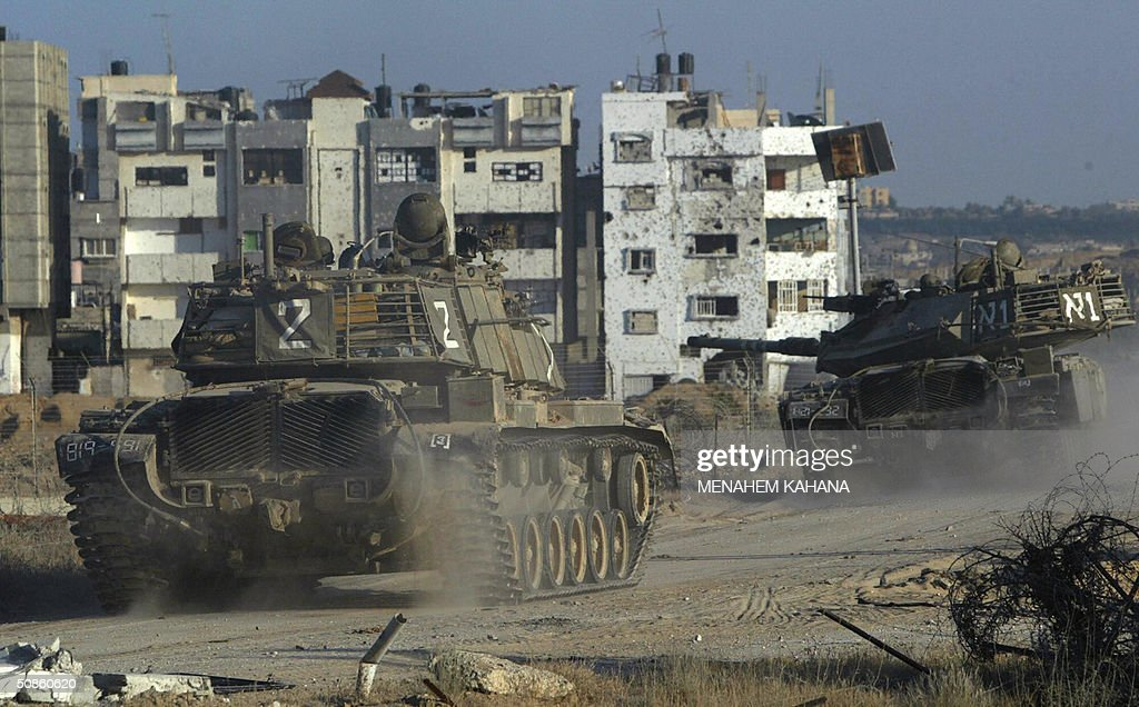 An Israeli tank convoy moves into the outskirts of the southern Gaza Strip town of Rafah 20 May 2004, on the third day of the massive Israeli army operation in the area. A total of 41 Palestinians have been killed since the Israeli army launched the Rafah raid early 18 May, dubbed 'Operation Rainbow' and aimed at stopping arms smuggling from Egypt through cross-border tunnels.