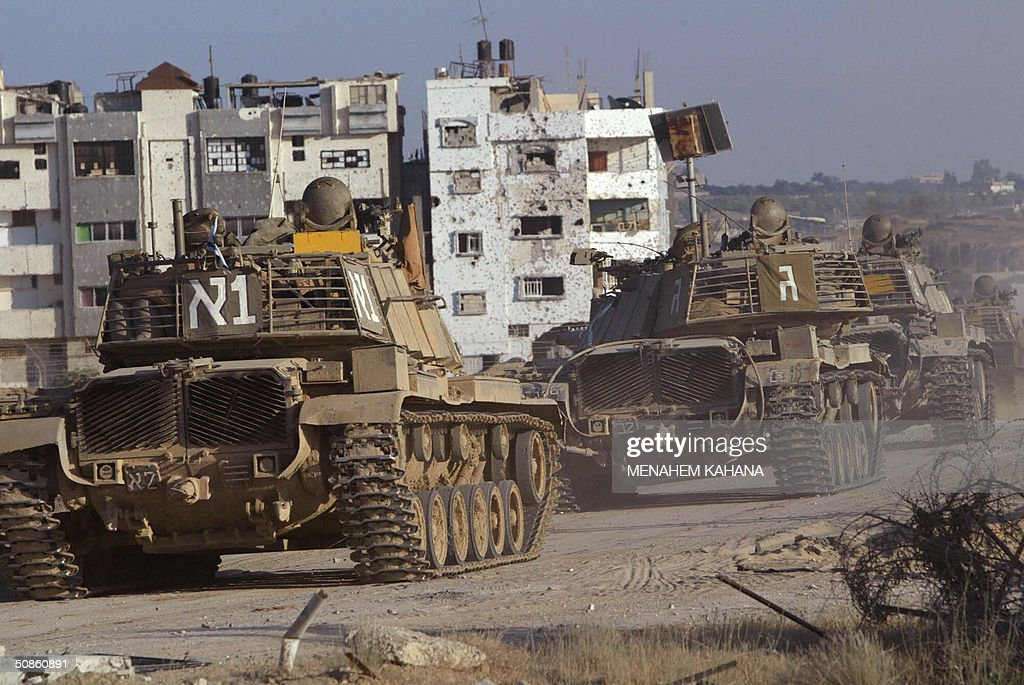 An Israeli tank convoy rolls into the outskirts of the southern Gaza Strip town of Rafah 20 May 2004, on the third day of the massive Israeli army operation in the area. A total of 41 Palestinians have been killed since the Israeli army launched the Rafah raid early 18 May, dubbed 'Operation Rainbow' and aimed at stopping arms smuggling from Egypt through cross-border tunnels.