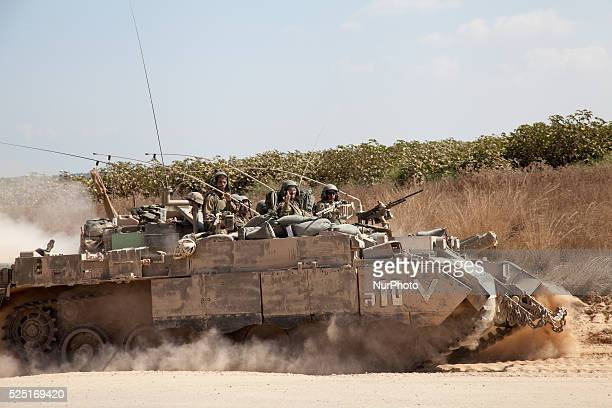 An Israeli tank crew wave as they go back into the fighting in the Gaza Strip