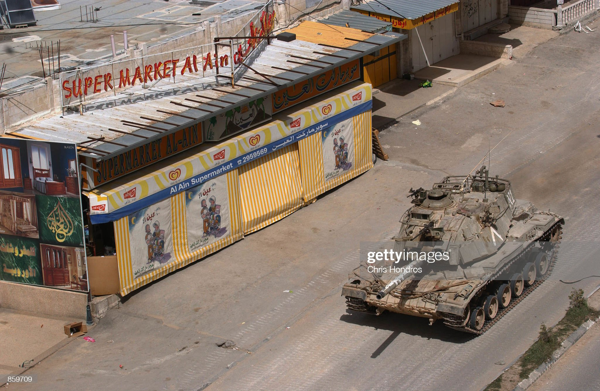 https://media.gettyimages.com/photos/an-israeli-tank-passes-by-a-closed-supermarket-april-11-2002-in-the-picture-id859709?s=2048x2048
