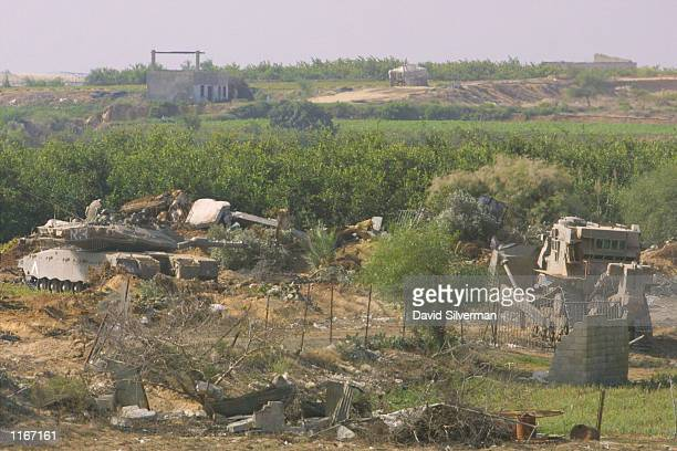 An Israeli tank stands guard as an armored bulldozer tears down Palestinian property October 3, 2001 in Beit Lahiya in the northern Gaza Strip...