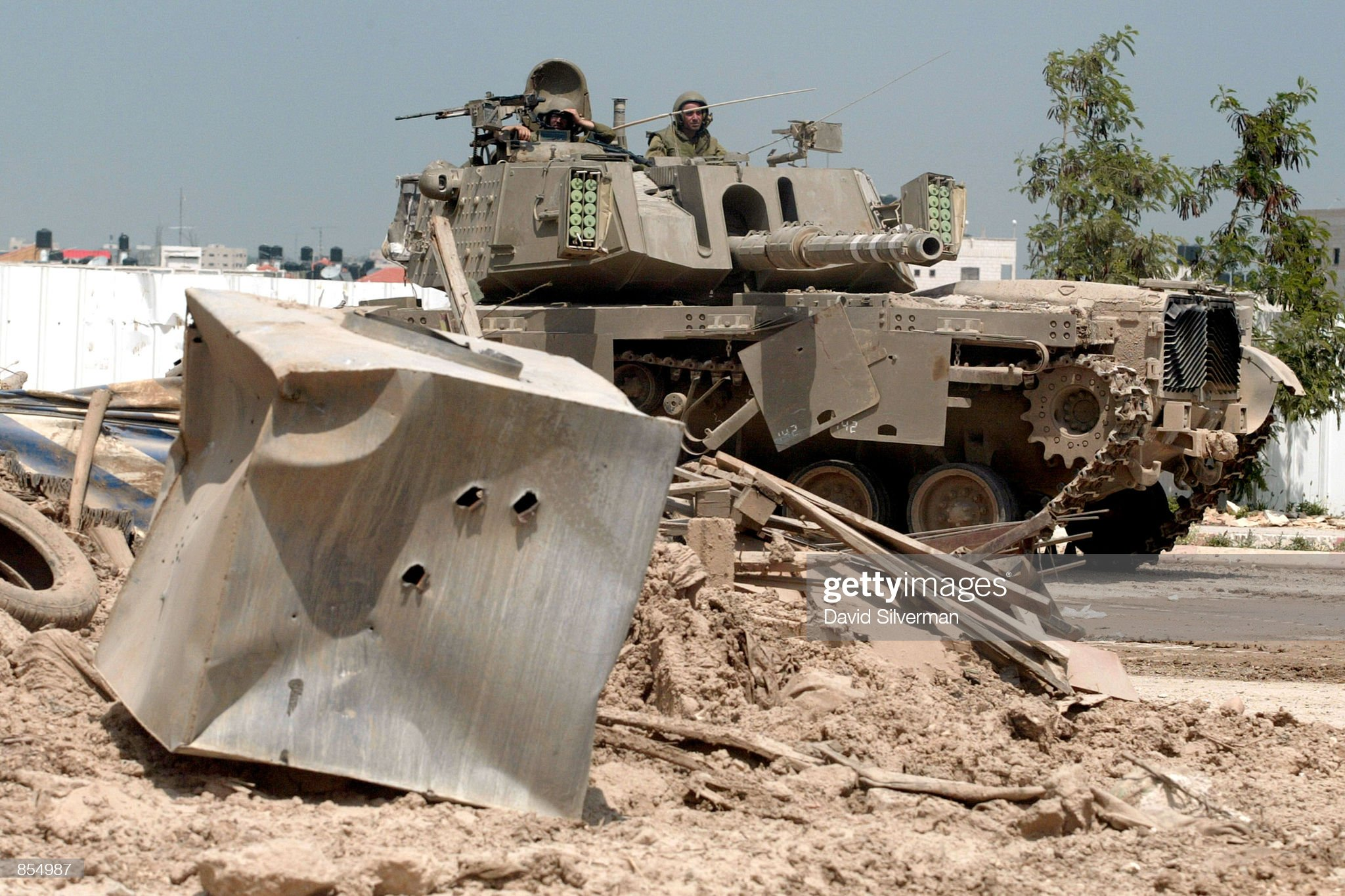 https://media.gettyimages.com/photos/an-israeli-tank-sticks-out-from-behind-a-mound-of-rubble-in-the-west-picture-id854987?s=2048x2048