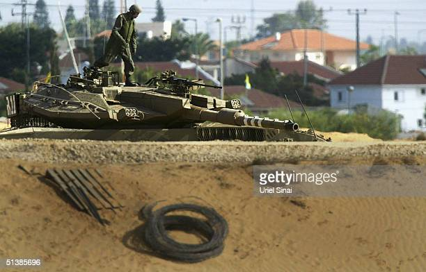 An Israeli tank takes position at the border between Nisanit and the Gaza Strip town of Beit Hanun October 3 2004 in Gaza Strip Israeli Prime...