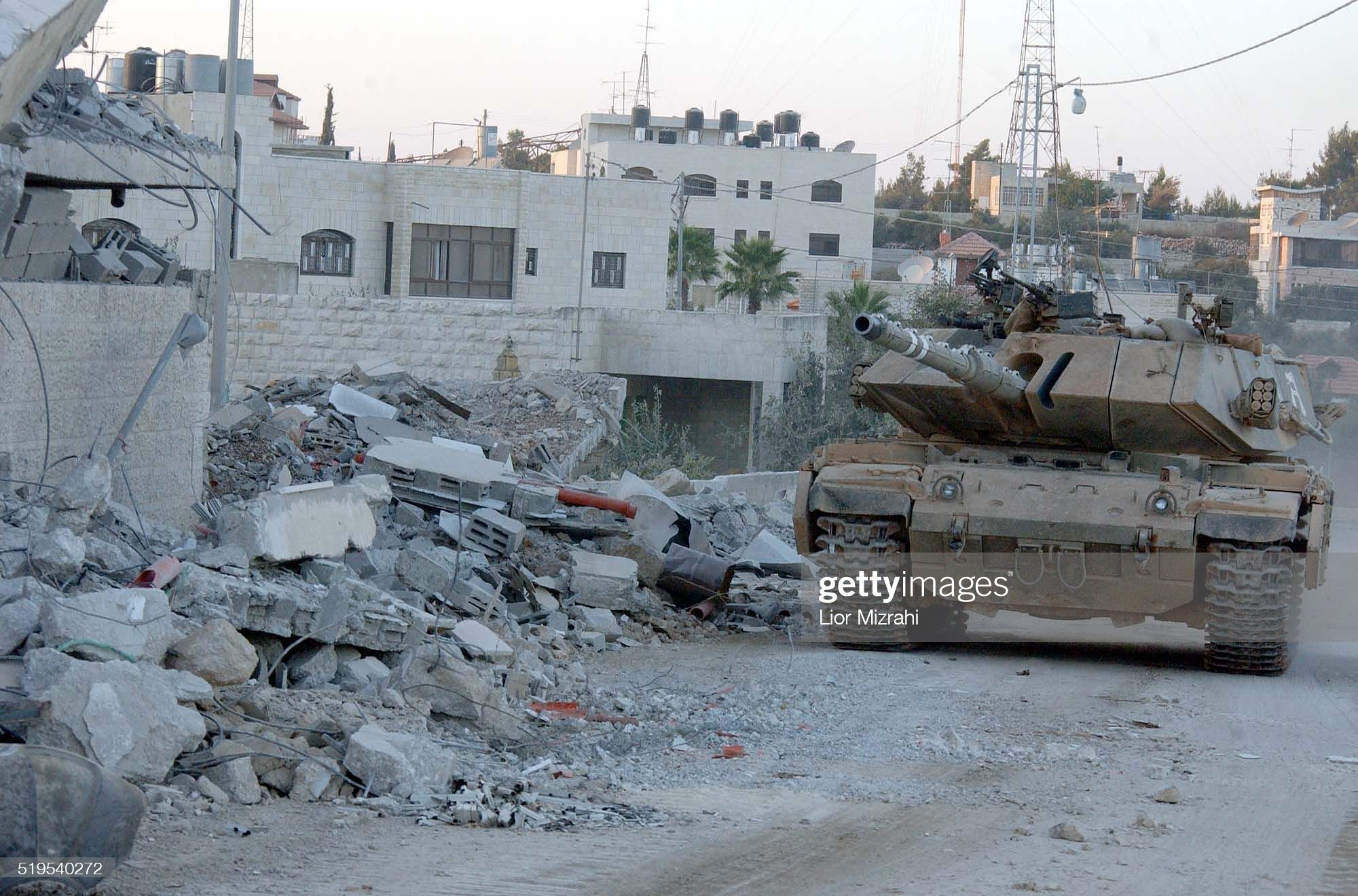 https://media.gettyimages.com/photos/an-israeli-tank-takes-up-position-next-to-the-damaged-compound-of-picture-id519540272?s=2048x2048