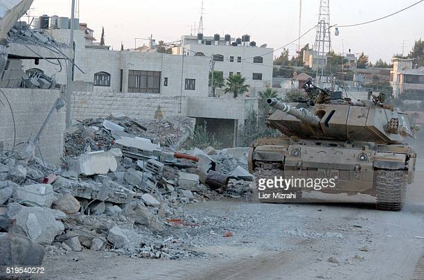 An Israeli tank takes up position next to the damaged compound of Palestinian President Yasser Arafat in the West Bank city of Ramallah September 22...