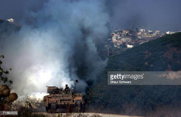 An Israeli tank uses a smoke screen to protect itself from anti tank missiles during an operation August 1 2006 on the Israeli side of the...