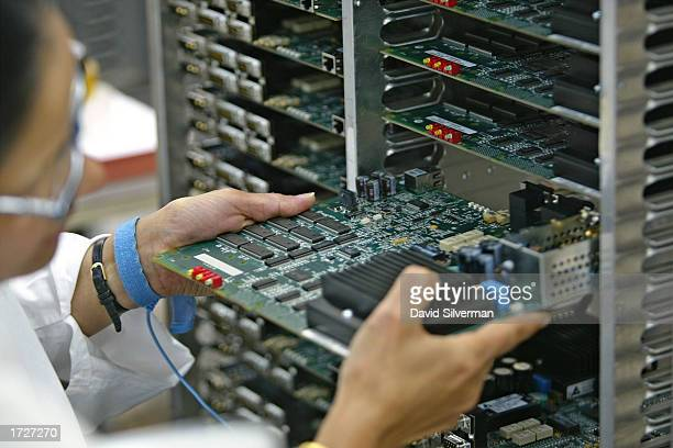 An Israeli technician slides a completed Micro SDM-1 card into a trolley at an ECI Telecom high-tech plant January 15, 2003 in Petah Tikva which is...