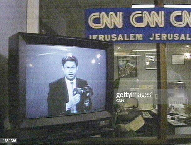 An Israeli television presenter demonstrates the proper use of a gas mask January 17 1991 in Jerusalem Israel This image was taken from inside CNN's...