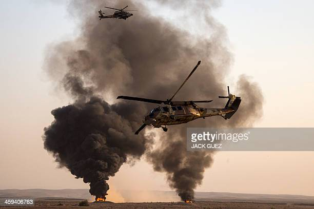 An Israeli UH60 Black Hawk and a AH64 Apache longbow helicopter perform during an air show at the graduation ceremony of Israeli air force pilots at...