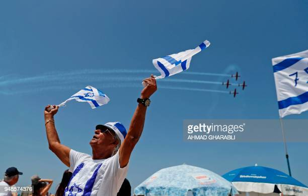 An Israeli waves Israeli flags as he dresses in flag morabilia while planes perform above during an air show as part of the 70th Independence Day on...