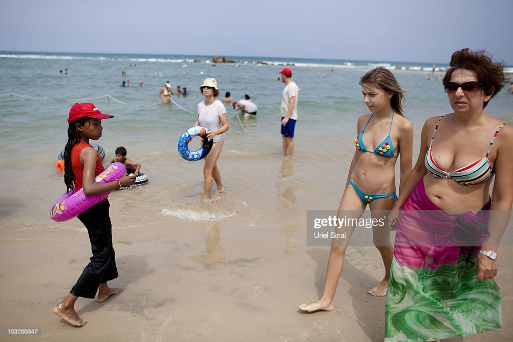 An Israeli woman and her daughter walk past Palestinian children from the West Bank village of Jahalin as they spend the day at the beach on August 2, 2010 in Bat Yam, Israel. A group of Israeli women organize a weekly visit for Palestinian children from all over the West Bank to the the Israeli seaside, for most of the children this is the first time they get to the beach.