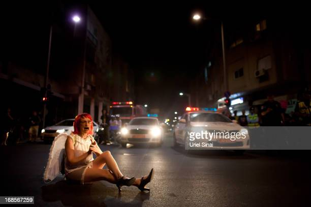An Israeli woman blocks a main road as demonstrators march through the streets to protest against Israeli Finance Minister Yair Lapid's budget cuts...