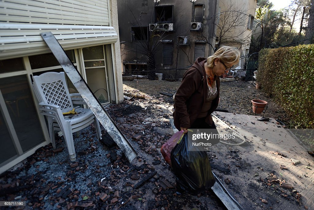 An Israeli woman carries some belongings from a burnt house, hit by a massive forest fire in the Northern city of Haifa, Israel on November 25, 2016. The massive fire in the city of Haifa lead to the evacuation of dozens of thousands of city residents and is part of a lrage wave of forest fires errupted all over Israel during the last days.