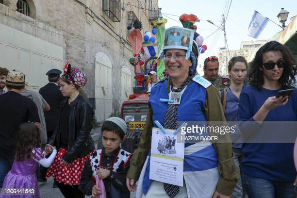 An Israeli woman dressed in a costume mocking Israel's centrist Blue and White political alliance and the Joint Arab list during celebrations of the...