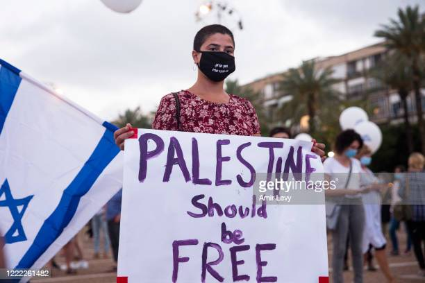 "An Israeli woman holds a sign that reads ""Palestine should be free"" as she protest against Israel goverment's plan to annex parts of the West Bank on..."