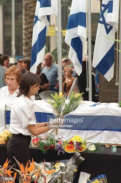 An Israeli woman lays flowers by the flag-draped coffin of Leah Rabin, wife of assassinated former Prime Minister Yitzhak Rabin, during a ceremony...