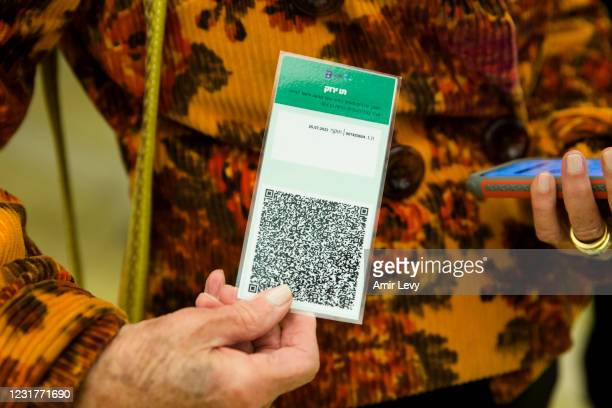 An Israeli woman presents a 'Covid19' vaccination certificate named 'Green Pass', before entering a musical performance at Tel Aviv's concert hall on...