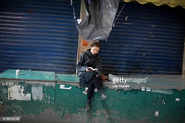 An Israeli woman reads a book at Mahane Yehuda open market on February 27 2014 in Jerusalem Israel The Mahane Yehuda Market is over 100 years old...