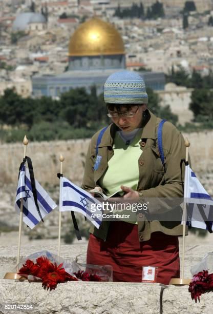 An Israeli woman reads a prayer by a grave of a fallen soldier at the military cemetery on the Mount of Olive overlooking the Dome of the Rock mosque...