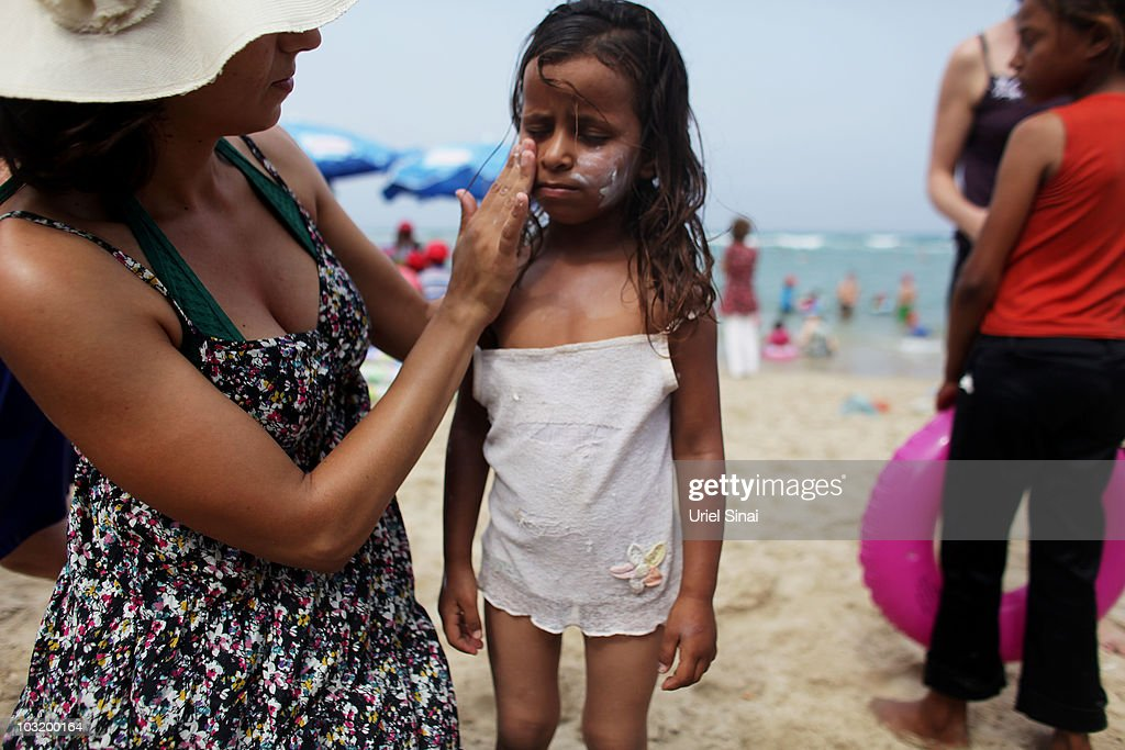 An Israeli woman rubs sunscreen on a Palestinian girl from the West Bank village of Jahalin as they spend the day at the beach on August 2, 2010 in Bat Yam, Israel. A group of Israeli women organize a weekly visit for Palestinian children from all over the West Bank to the the Israeli seaside, for most of the children this is the first time they get to the beach.