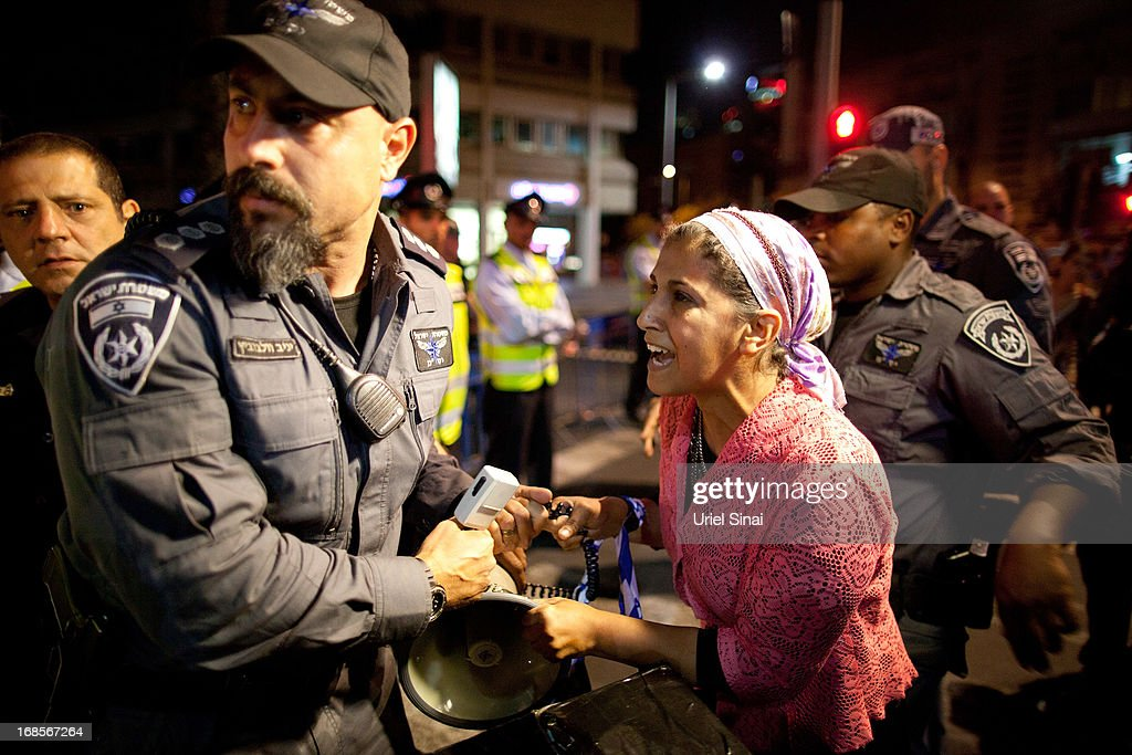 An Israeli woman scuffles with a policeman as demonstrators march through the streets to protest against Israeli Finance Minister Yair Lapid's budget cuts on May 11, 2013 in Tel Aviv, Israel. Thousands of Israelis took to the streets to protest against austerity measures presented this week as part of the state's new budget.