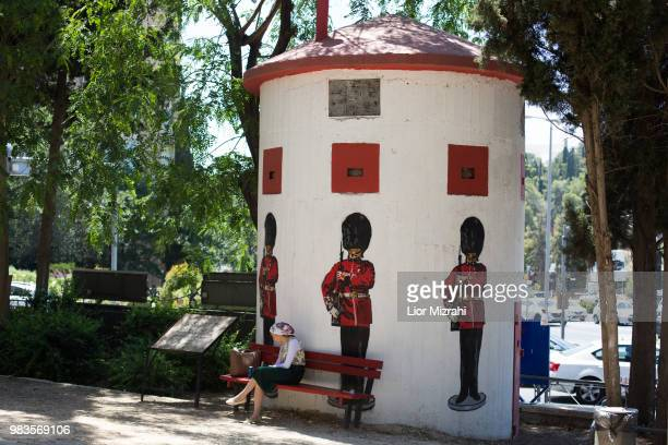An Israeli woman sits next to an old British military Pillbox with pictures of Grenadier Guards on June 25 2018 in Jerusalem Israel Britain's Prince...