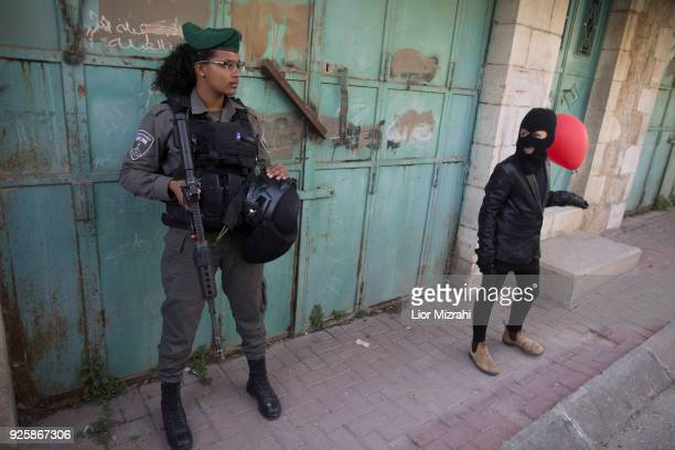 An Israeli woman soldier stand gaurds gaurd as Israelis take part in a parade celebrating the Jewish holiday of Purim on March 1 2018 in Hebron West...