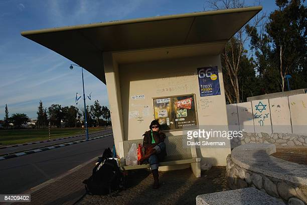 An Israeli woman stays close to a reinforced bomb shelter as she waits for a bus out of town on January 8, 2009 in the southern Israeli town of...