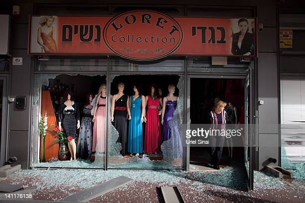 An Israeli woman surveys the damage to her store following a rocket attack from the nearby Gaza Strip on March 12 2012 in Ashdod Israel The UN and EU...