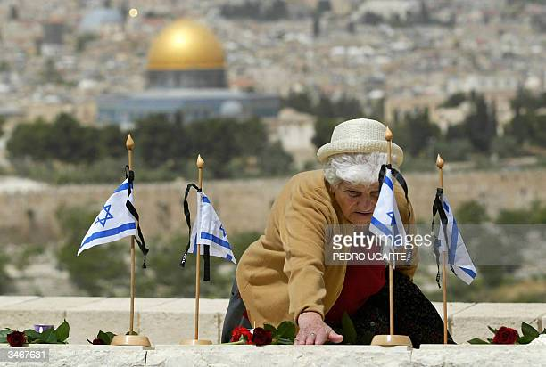 An Israeli woman touches a grave of an Israeli killed during the 1948 war as the Dome of the Rock mosque appears in the background at the military...