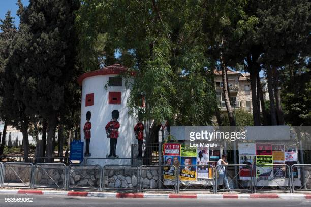 An Israeli woman walks next to an old British military Pillbox with pictures of Grenadier Guards on June 25 2018 in Jerusalem Israel Britain's Prince...