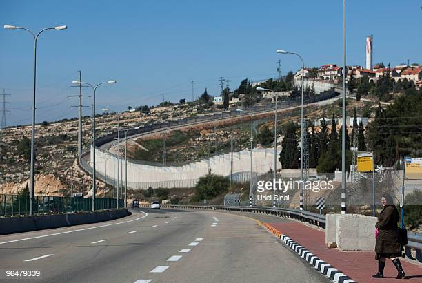 An Israeli woman walks to a bus station on route 443 a main road on which Palestinian traffic is forbidden linking central Israel with Jerusalem as...