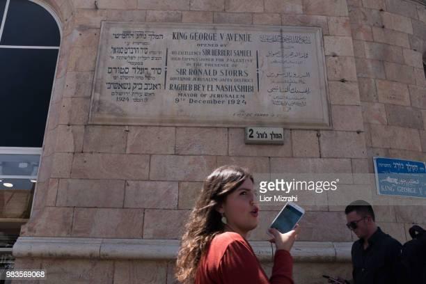 An Israeli woman walks under a dedication plaque in honor of King George V in King George street in downtown on June 25 2018 in Jerusalem Israel...