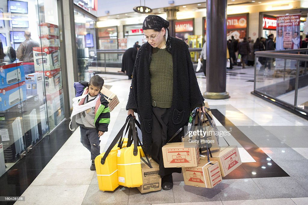 An Israeli woman walks with her child after collectiong gas mask kits from a distribution station in a mall January 31, 2013, in Pisgat Ze'ev, East Jerusalem, Israel. Israel remains on high alert after the Israeli air force reportedly launched an airstrike January 30, on a convoy that Israeli officials said was carrying weapons from Syria to Lebanon on the Syria-Lebanon border.
