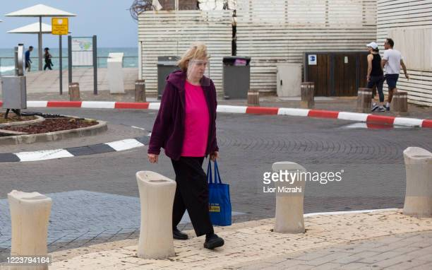 An Israeli woman wearing a protective mask walks on the beach promenade on May 9, 2020 in Tel Aviv, Israel. Israel is preparing to reopen markets and...