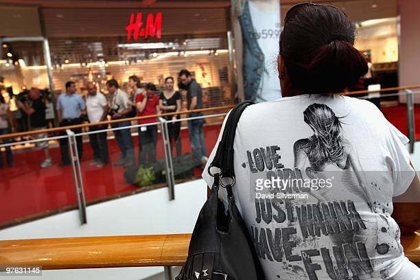 An Israeli woman wears a shirt with a slogan as she waits for hours outside the new H M outlet of the Swedishbased clothing chain for it to open on...