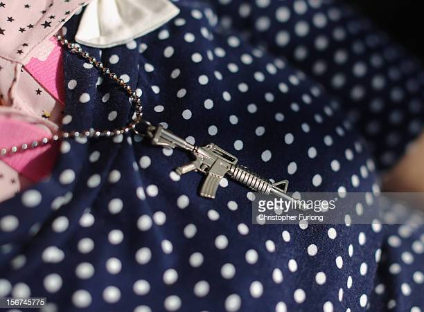 An Israeli woman wears a trinket in the shape of an M16 rifle as she sits in a cafe on November 20 2012 close to Israel's border with the Gaza Strip...
