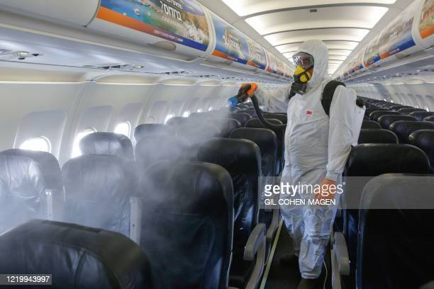 An Israeli worker in full hazmat suit sprays disinfectant in the cabin of an Israir Airlines Airbus A320 airplane, at the Ben Gurion International...