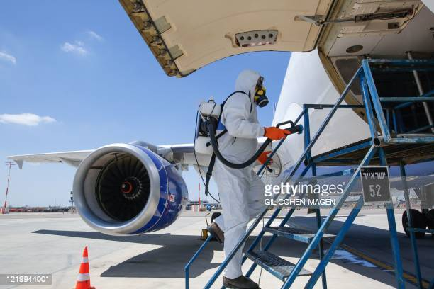 An Israeli worker in full hazmat suit sprays disinfectant in the cargo hold of an Israir Airlines Airbus A320 airplane, at the Ben Gurion...