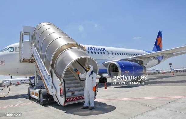 An Israeli worker in full hazmat suit sprays disinfectant on the boarding stairs of an Israir Airlines Airbus A320 airplane, at the Ben Gurion...