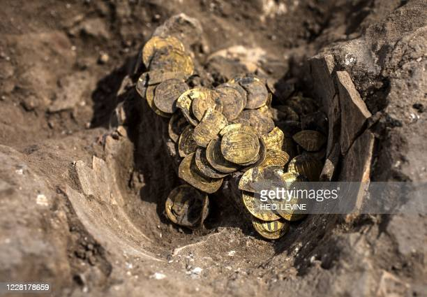 An Israeli worker unearthes gold coins dating to the Abbasid Caliphate, during a press presentation of the discovery at an archeological site near...
