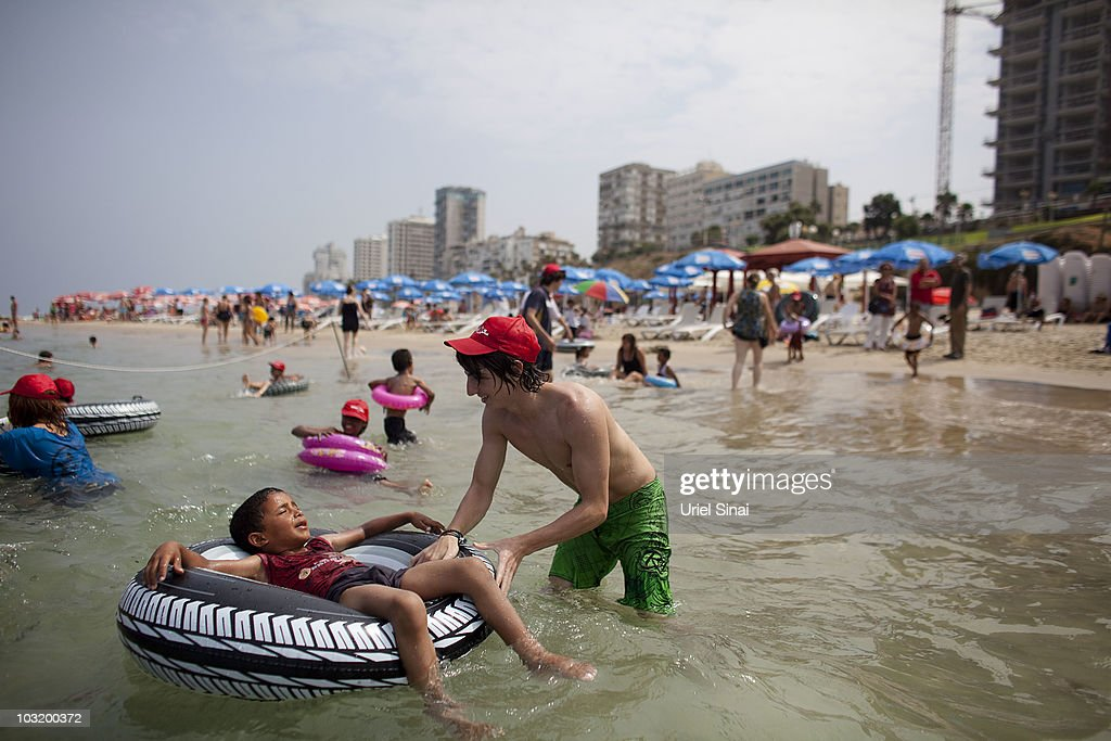 An Israeli youth plays with a Palestinian boy from the West Bank village of Jahalin, as they spend the day at the beach on August 2, 2010 in Bat Yam, Israel. A group of Israeli women organize a weekly visit for Palestinian children from all over the West Bank to the the Israeli seaside, for most of the children this is the first time they get to the beach.