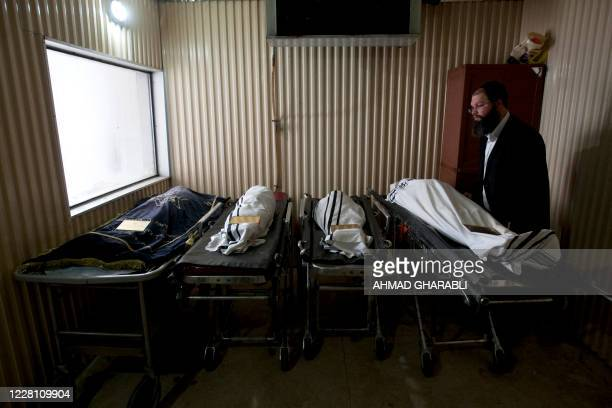An Israeli Zaka Volunteer stands next to the bodies of victims of the shooting in a morgue before their funeral in Jerusalem on March 21 2012 The...