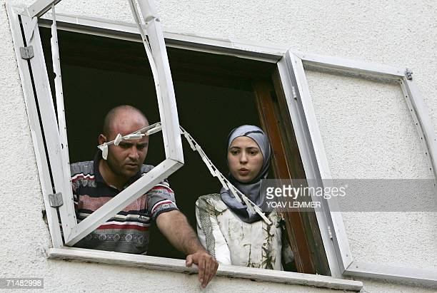 An Israeli-Arab man and woman look out from a window at the shrapnel holes left by a rocket fired by Hezbollah which slammed into the nearby street...