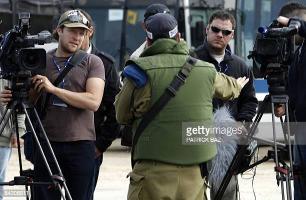 An Isreali army military police officer orders cameramen to move from the Israeli side of the Erez crossing with the Gaza Strip on January 8 2009 to...